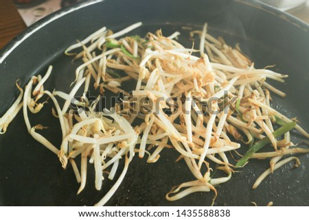 fried bean sprouts with smoke on black pan close up shot