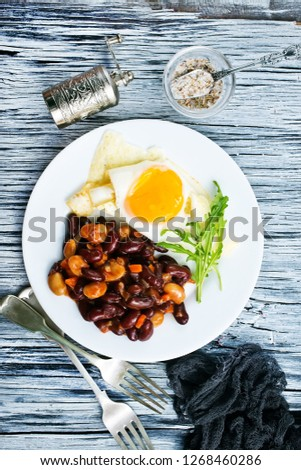 fried bean with fried eggs on plate for breakfast