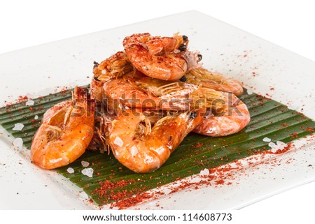 fried black tiger prawns with herbs and spices on banana leaf