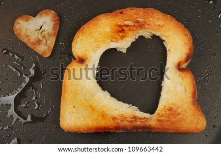 Fried bread with a heart shaped cut out and heart shaped fried potato in an oily frying pan