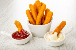Fried breaded chicken stick in sauce boat with ketchup, few fried breaded chicken sticks in white bowl, chicken stick in mayonnaise on wooden table