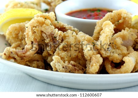 Fried Calamari lightly breaded served with marinara sauce and lemon ...