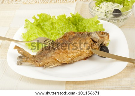 fried carp and early cabbage salad on the table