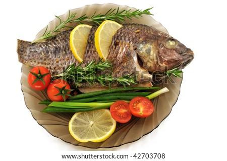 Fried carp on a plate with tomatoes, lemon, onion and rosemary
