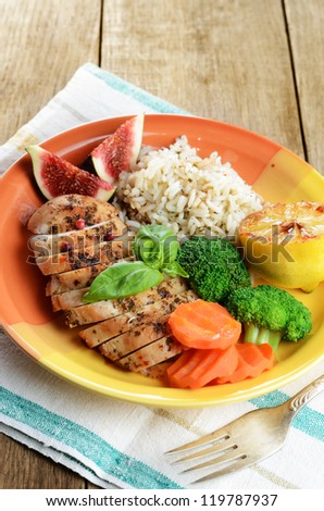Fried chicken breast with rice, vegetables and figs on the wooden table