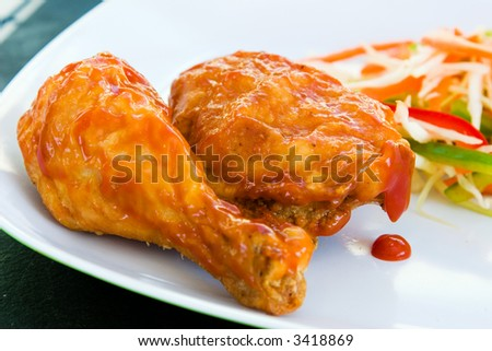 Fried chicken covered with tomato sauce - a caribbean specialty, served with grated vegetables. Shallow DOF.