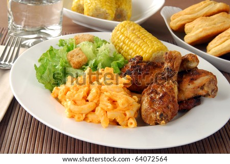 Fried chicken drumsticks with salad and macaroni and cheddar cheese