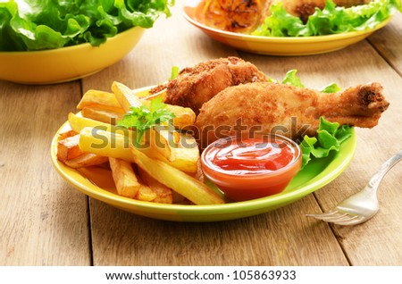 Fried chicken legs with french fries on the table