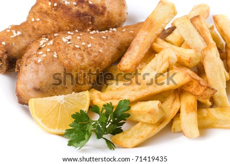 Fried chicken legs with lemon and potato served on the white plate