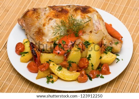 Fried chicken legs with vegetables served on the white plate