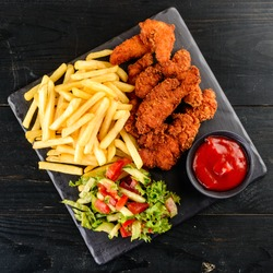Fried chicken, nuggets and french fries, set of chicken nuggets, salad and french fries on wood table. top view
