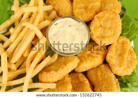 Fried chicken nuggets with french fries and sauce close-up