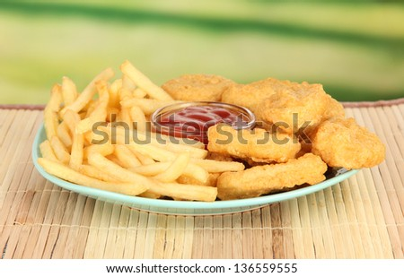 Fried chicken nuggets with french fries and sauce on table in park