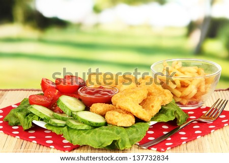 Fried chicken nuggets with french fries,vegetables and sauce on table in park