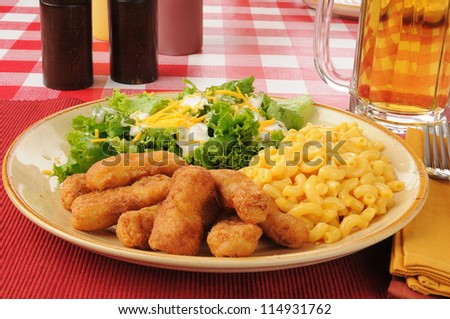 Fried chicken strips and a mug of beer with macaroni and cheese