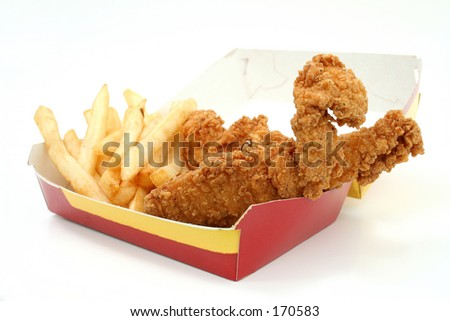Fried chicken strips and fries in a red and yellow box.  Focus on chicken strip and corner of box.