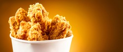 Fried Chicken wings and legs. Bucket full of crispy kentucky fried chicken on brown background.