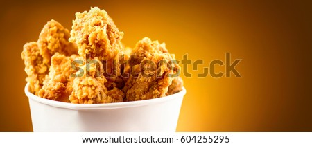 Fried Chicken wings and legs. Bucket full of crispy kentucky fried chicken on brown background. #604255295