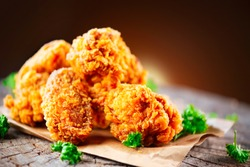 Fried chicken wings and legs on wooden table. Breaded Crispy fried kentucky chicken tasty dinner. Close up of tasty and juicy fried chicken.