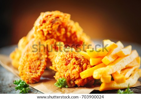 Fried chicken wings and legs with french fries on wooden table. Breaded Crispy fried kentucky chicken tasty dinner with fried potato.
