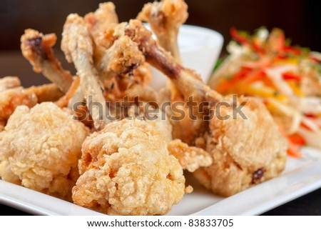 Fried chicken wings garnished with fresh vegetables with Teriyaki sauce