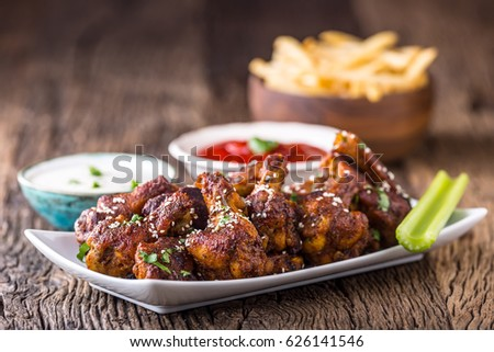 Fried chicken wings in white bowl dressing ketchup and potato fries.
