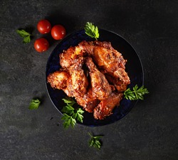 Fried chicken wings on rustic serving board, spicy tomato sauce, herbs and mug of light beer over black wooden backdrop, top view
