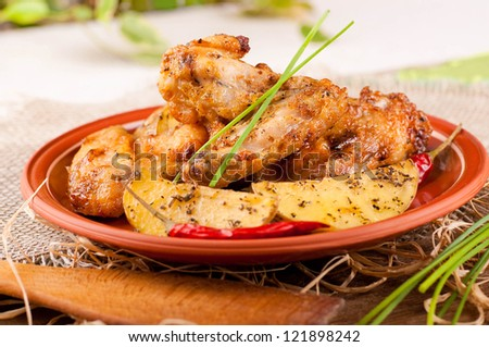 Fried chicken wings with baked potatoes