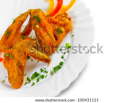 Fried chicken wings with legs his chopped pepper, onion and fennel on a plate isolated on white background