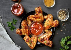 Fried chicken wings with sauce on dark background. Top view, flat lay.