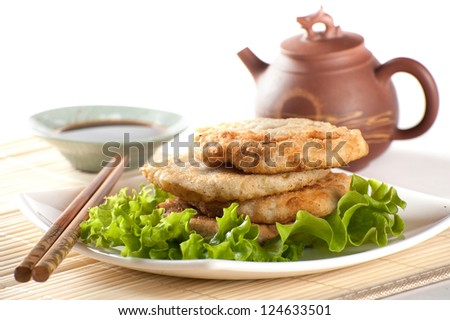 Fried chinese pancakes served with salad leaves with tea and soy sauce