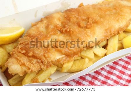 Fried cod & chips in cardboard takeaway carton.