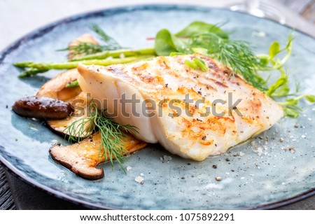 Fried cod fish filet with green asparagus and mushrooms as close up on a plate