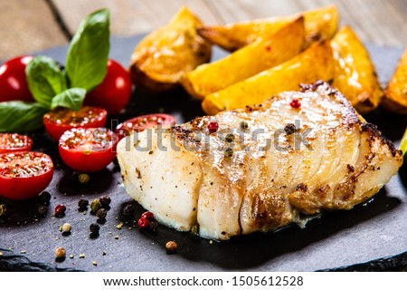 Fried cod loin with baked potatoes and vegetables