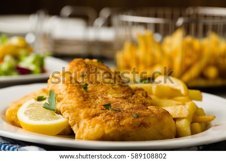 Fried cod with french fries on white plaet.