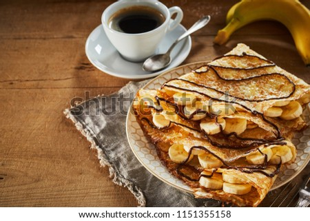 Fried crispy banana pancakes drizzled with chocolate and castor sugar served for breakfast with espresso coffee on a rustic table with copy space