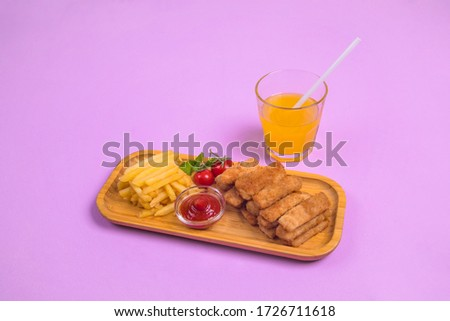 Fried crispy chicken nuggets with french fries and ketchup on  board. Orange juice. Pink background. Жареные хрустящие куриные наггетсы с кетчупом и картошкой фри. Апельсиновый сок. Розовый фон. Сток-фото ©