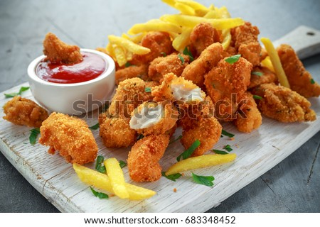 Fried crispy chicken nuggets with french fries and ketchup on white board Сток-фото ©