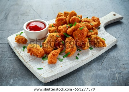 Fried crispy chicken nuggets with ketchup on white board