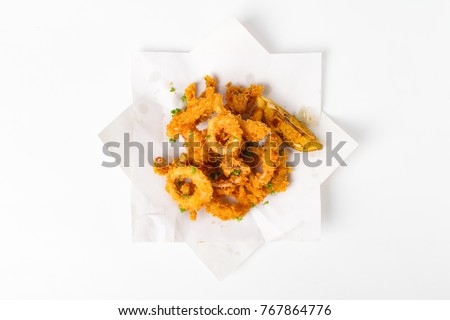 Fried crispy squid rings breaded ( caramari ) with lemon top view in a paper on white backgruond Сток-фото ©