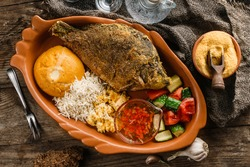 Fried dorado fish with polenta, cheese, scrabble eggs and vegetables on rustic wooden background with Russian vodka drink. Traditional Romanian food, top view