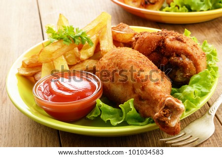 Fried drumsticks with french fries on the table