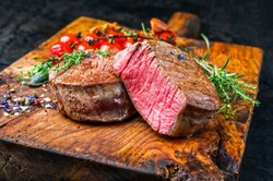 Fried dry aged beef fillet medallion steak natural with tomatoes and herbs as closeup on a wooden cutting board