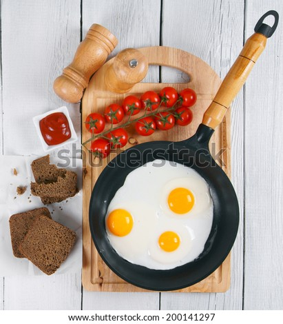 Fried egg in a frying pan, a saltcellar and tomatoes on a chopping board. Rye bread and ketchup on a paper. On a wooden background.