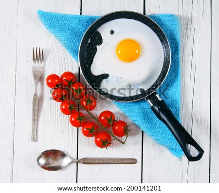Fried egg in a frying pan on a blue towel, tomatoes and tablewares. On a wooden background.