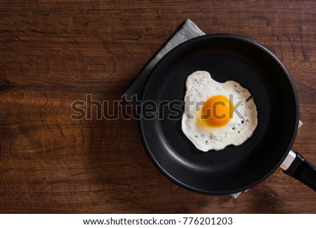 Fried egg in a frying pan on the brown wooden table background. with copy space. top view. #776201203