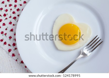 Fried egg in a heart shape in a white plate with a fork on white background