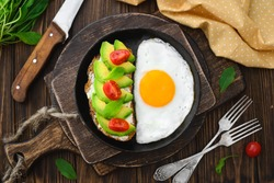 Fried Egg in pan and vegan avocado sandwiches top view close-up in rustic style on a wooden background, cutting boards, forks, knife, arugula, concept of a healthy lifestyle