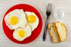 Fried egg in red glass plate, fork, salt shaker, slices of bread on wooden table. Top view
