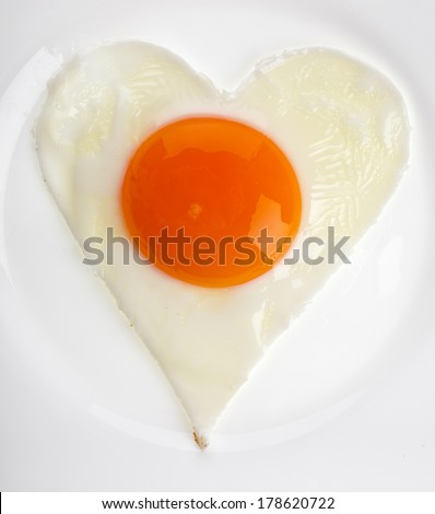 fried egg in shape of heart on a white plate close up surface background